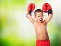 A little kid wearing a boxer gloves